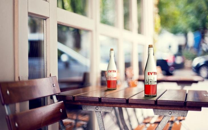 Projekt: Láhev EVYN na stole na terase